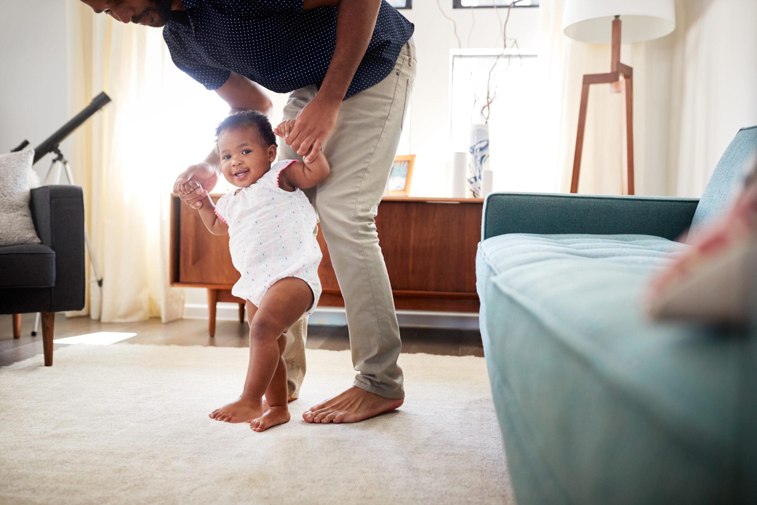 padre feliz con su hija enseñandole a dar sus primeros pasos en casa